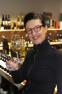 Sylvie tenant un verre vin blanc interieur magasin