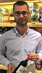 Yvonnick tenant une bouteille de vin